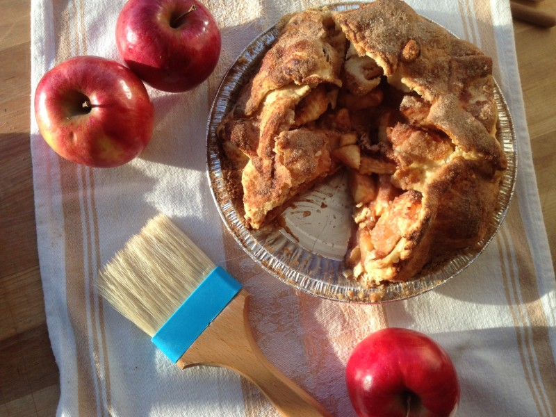 Apple pie with one slice cut out and apples around it