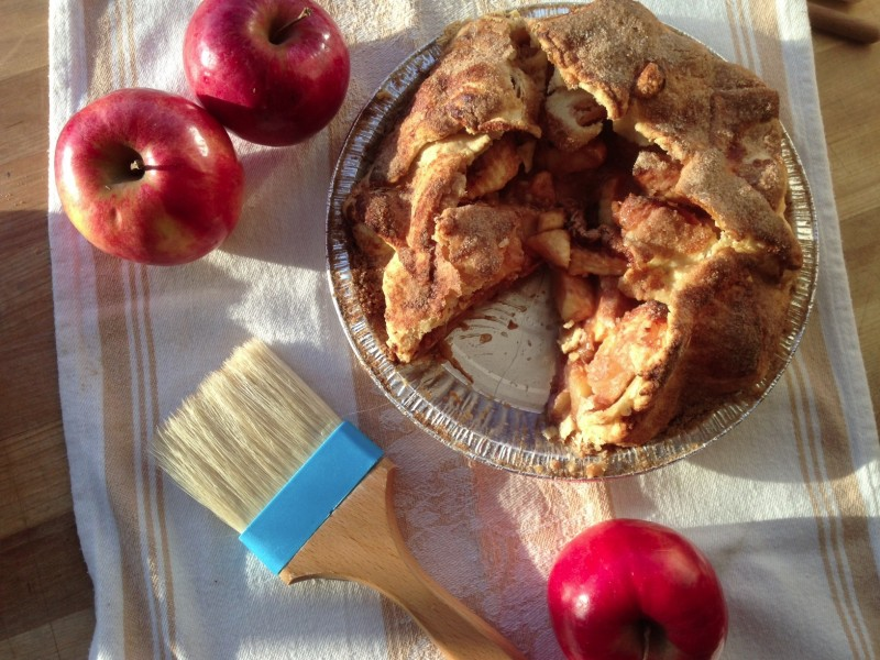 apple pie with slice taken out surrounded by apples