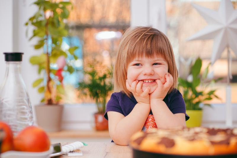 toddler smiling in front of food